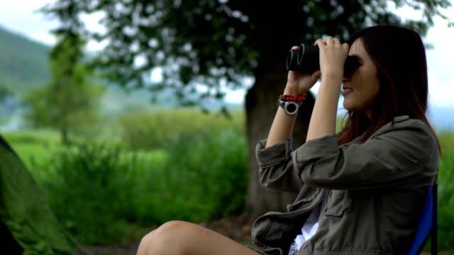 vídeos de stock e filmes b-roll de asian women using binoculars on the camp site - observar pássaros