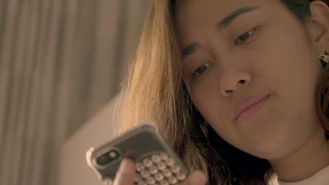 asian women using mobile phone at home - solo una donna di età media video stock e b–roll