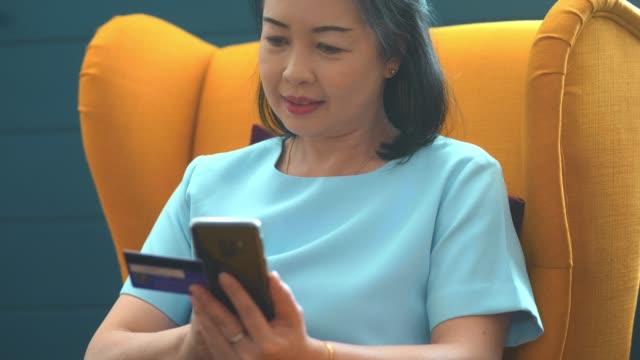 vídeos y material grabado en eventos de stock de las mujeres asiáticas que usan el pago del teléfono móvil - pago por móvil