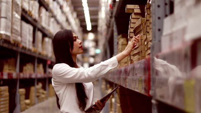 アジアの女性倉庫でデジタルタブレットを使用しています。在庫の注文の確認 - 貯蔵庫点の映像素材/bロール