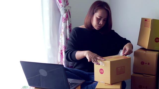 アジアの女性を使用して携帯電話の顧客から電子メール受信トレイの順序を確認します。オンライン ショッピング - e mail点の映像素材/bロール