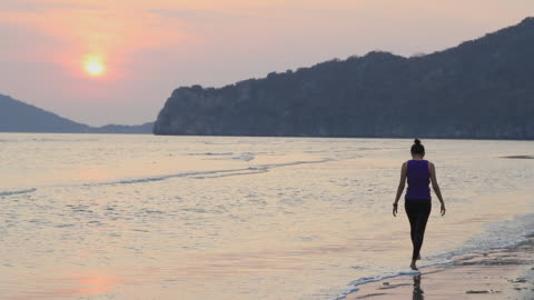 asian women walking running and exercise alone on a sand beach by the sea and mountain background in the sunrise morning. exercise and meditation concept.slow motion. - twilight stock videos & royalty-free footage