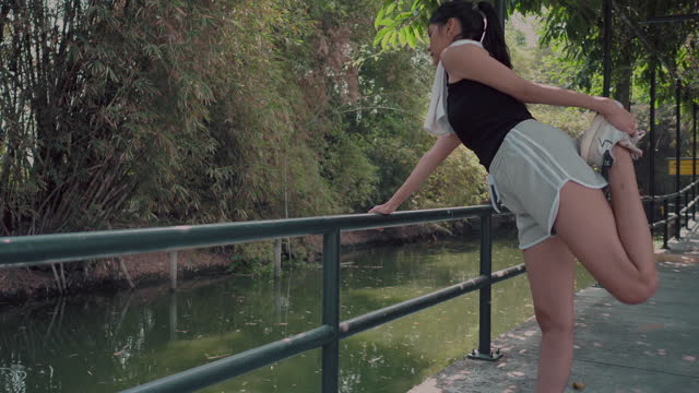 stockvideo's en b-roll-footage met asian women warm up before exercising - jogster