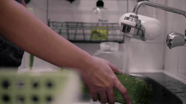 アジアの女性は台所で皿、眼鏡、水筒を洗います。 - 容器点の映像素材/bロール