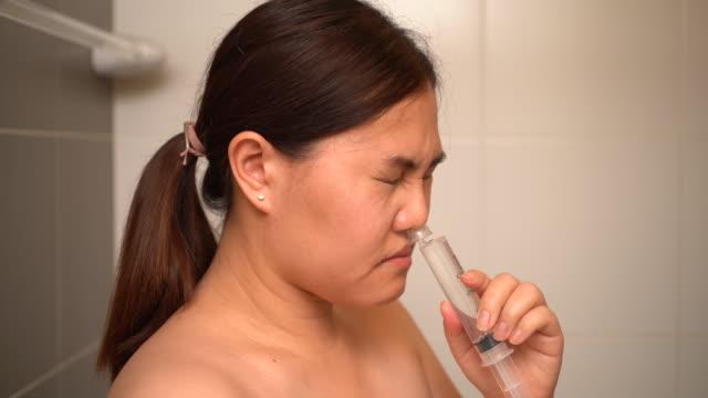 塩水で彼女の鼻を洗うアジアの女性 - 鼻腔点の映像素材/bロール