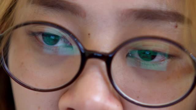 Asian women watching screen, reflection in glasses
