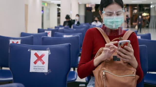 asiatische frauen tragen maske und gesicht, um sich zu schützen, wenn sie mit dem flugzeug reisen. - flugpassagier stock-videos und b-roll-filmmaterial