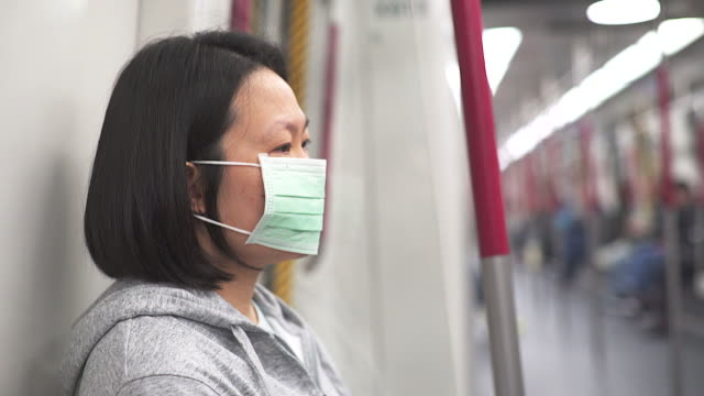 Asian women wear mask to protect germ during transportation by train.