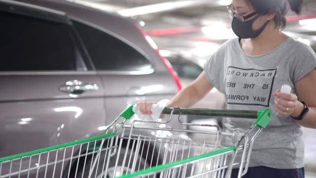 asiatiska kvinnor bär ansiktsmask med alkohol gel torka ner på handtagen ytor i snabbköpet vagnen för rengöring coronavirus covid-19 i snabbköpet parkering. - parkera bildbanksvideor och videomaterial från bakom kulisserna
