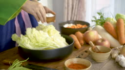 Asian women wearing hanbok Korean traditional costumes are cooking Kimchi
