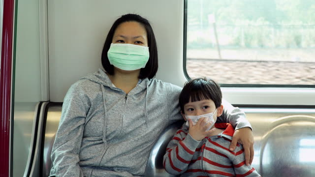 vídeos de stock e filmes b-roll de asian women with her son wear mask to protect germ during transportation by train. - máscara de proteção