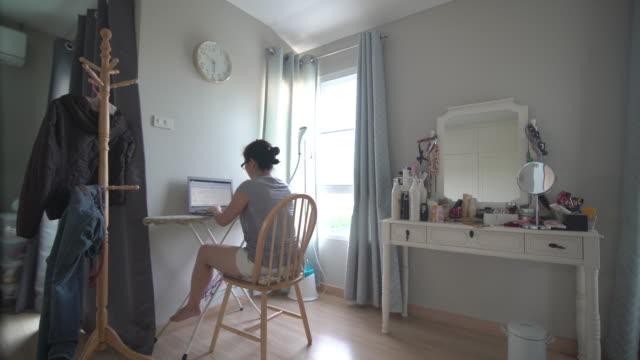 自宅の楽屋で新しいワークスペースを持つアジアの女性 - アイロン台点の映像素材/bロール