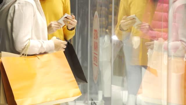 店の窓を見ている買い物袋を持つアジアの女性。 - 見せる点の映像素材/bロール