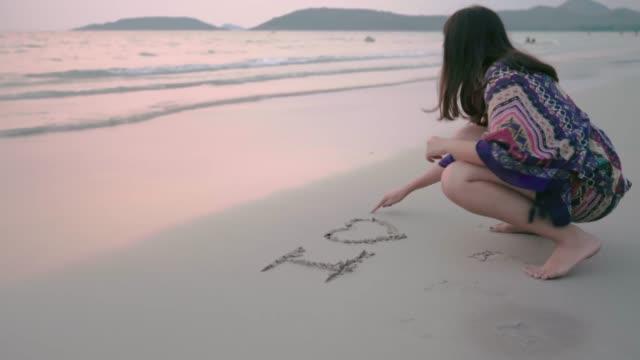 """Mujeres asiáticas escribiendo palabra """"te amo"""" en la arena en la playa al atardecer"""
