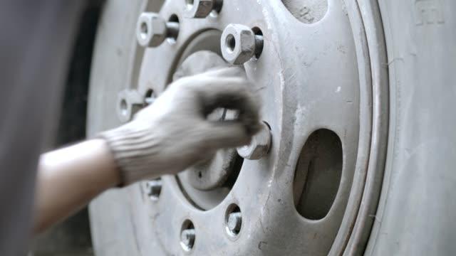 vidéos et rushes de travailleur asiatique pendant serrer des écrous de roue par le pistolet lourd d'air, les pneus de timbre par le nombre en acier de chaleur, pneu d'assemblage par le mouvement lent manuel.4k. - poids lourd