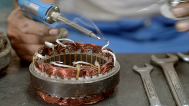 asian worker during used solder iron for repairing armature coil of alternator truck car.4k slow motion. - electrical equipment video stock e b–roll