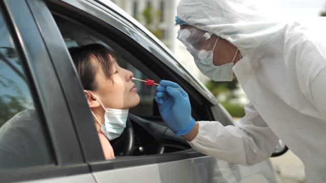asian worker performing drive-thru covid-19 test taking nasal swab specimen sample from male patient through car window,pcr diagnostic for coronavirus presence, doctor in ppe holding test kit - test drive stock videos & royalty-free footage