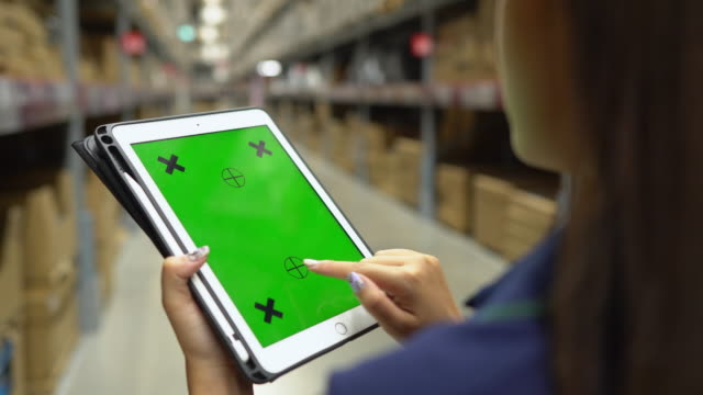 asian worker women checking stock in a distribution warehouse while holding green screen tablet. chroma key - cheque financial item stock videos & royalty-free footage