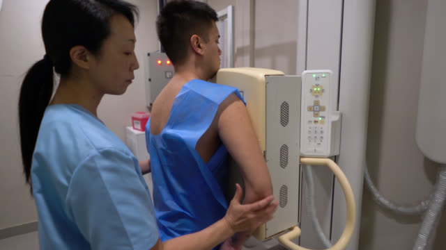 asian x-ray technician getting ready a patient for a chest xray - chest torso stock videos & royalty-free footage