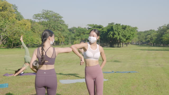 asian yoga class students woman wearing masks arriving and greeting by elbow bump to instructor and each other and stretching, warming up for class - exercise class stock videos & royalty-free footage