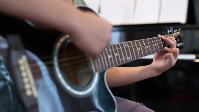 Asian young boy learning to play a Guitar