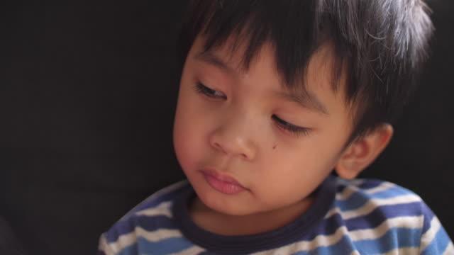vídeos de stock e filmes b-roll de asian young boy sleepy on sofa - bocejar