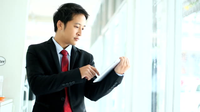 Asian young businessman working on tablet