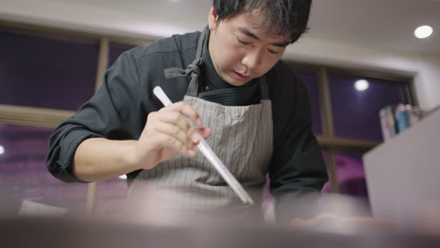 slo mo: asian young chef putting ingredients in tom yum soup into clay pot for serving. - one mid adult man only stock videos & royalty-free footage
