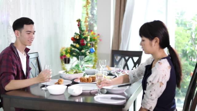 ロマンチックなディナーの夜を楽しんでいるアジアの若いカップルが一緒にキッチンにダイニング テーブルに座って飲み物 - 食事する点の映像素材/bロール