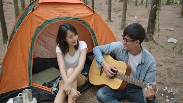 asian young couple enjoying camping in the pine forest - pinaceae stock videos & royalty-free footage