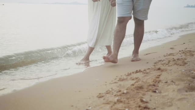 vídeos de stock e filmes b-roll de asian young couple holding hands and walking on beach - lua de mel