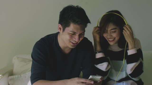 asian young couple listening music from podcast togetherness - personal stereo stock videos & royalty-free footage