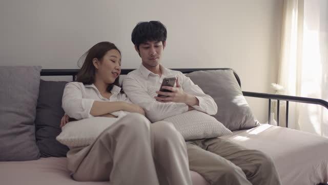 vídeos y material grabado en eventos de stock de pareja joven asiática mirando el teléfono móvil - 25 29 años