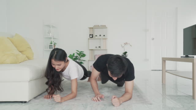 asian young couple man and woman in sports clothing doing plank during workout in living room at home to get exercise into her daily routine while social distancing. - bodyweight training stock videos & royalty-free footage
