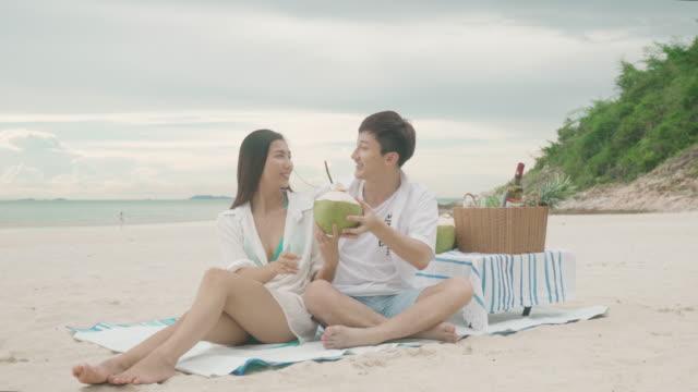 vídeos y material grabado en eventos de stock de pareja joven asiática sentada en la manta de picnic y bebiendo agua de coco en la playa y cerca del mar con frutas tropicales de fondo. concepto de verano, vacaciones, vacaciones y gente feliz en tailandia - cesta de picnic