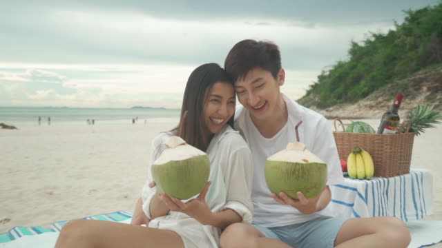 asian young couple sitting on the picnic blanket and drinking coconut water in the beach and near sea with tropical fruit in background. summer, holidays, vacation and happy people in thailand concept - bedclothes stock videos & royalty-free footage