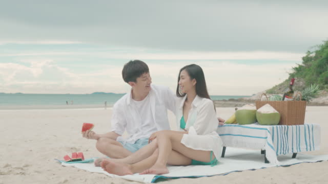 asian young couple sitting on the picnic blanket and eating watermelon in the beach and near sea with tropical fruit in background. summer, holidays, vacation and happy people in thailand concept - bedclothes stock videos & royalty-free footage