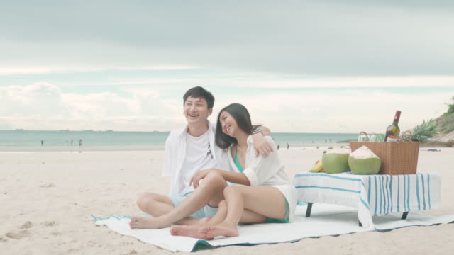 asian young couple sitting on the picnic blanket and relax in the white sand beach and near sea with tropical fruit in background. summer, holidays, vacation and happy people in thailand concept - bedclothes stock videos & royalty-free footage