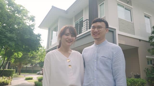 vidéos et rushes de jeunes couples asiatiques restants et étreignant ensemble regardant heureux devant leur nouvelle maison pour commencer une nouvelle vie. la famille, l'âge, la maison, l'immobilier et le concept de personnes. - new age concept