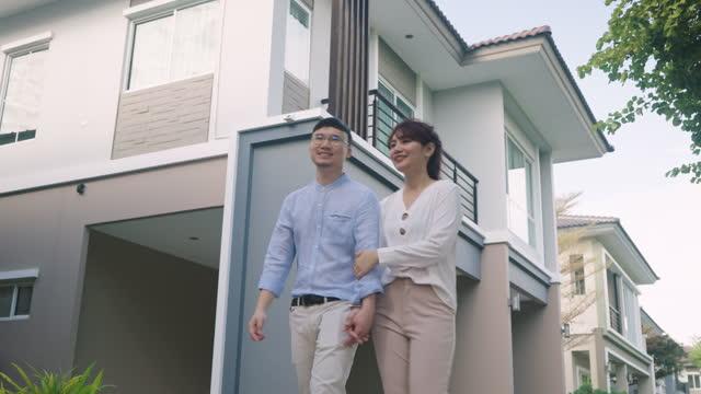 vidéos et rushes de jeunes couples asiatiques marchant et étreignant ensemble regardant heureux devant leur nouvelle maison pour commencer une nouvelle vie. la famille, l'âge, la maison, l'immobilier et le concept de personnes. - new age concept