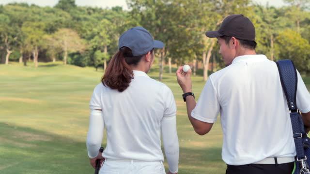 vidéos et rushes de jeunes couples asiatiques jouant au golf marchant le long du sac de golf de porte-ciel. succès, travail d'équipe, collaboration, soutien, style de vie, ensemble.confiance, leadership, puissance, compétence, force, amitié, concept. sports cinemagraphs.p - terrain de golf