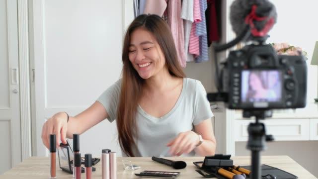 アジアの若い女性ブロガーをウイルスをソーシャル メディア concept.live ストリーミングのホーム オンライン インフルエンサーでメイク化粧品とビデオブログの録画 - マイク点の映像素材/bロール