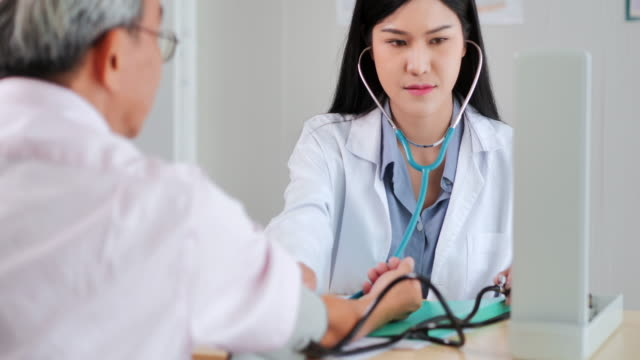 asian young female doctor checking heart to asian elderly men at hospital to prevent epidemics of coronavirus or covid19.older people healthcare,medical,caretaking,care,retirement,volunteer,lifestyle,healthcare and medicine,coronavirus or covid-19 - life insurance stock videos & royalty-free footage