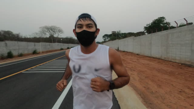 asian young fitness sport man running and he wears a mask for protective dust and pollution and protection flu virus, influenza, coronavirus on city - running stock videos & royalty-free footage