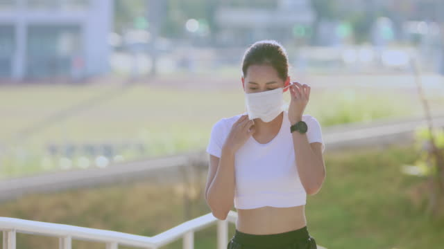 vídeos de stock, filmes e b-roll de mulher asiática jovem fitness esporte mulher correndo e ela usa uma máscara para proteção poeira e poluição na cidade - mulheres jovens