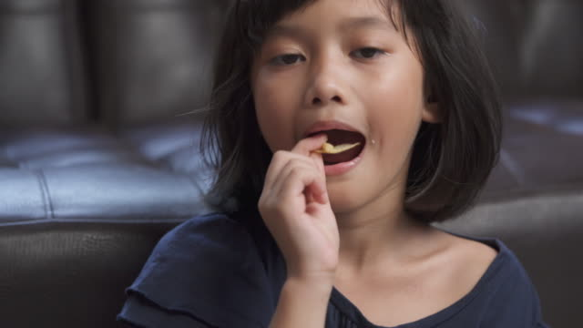 asian young girl enjoy eating cracker at home - cereal plant stock videos & royalty-free footage