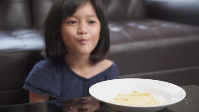 vídeos y material grabado en eventos de stock de chica joven asiática disfruta comiendo patatas fritas en casa - patatas fritas de churrería