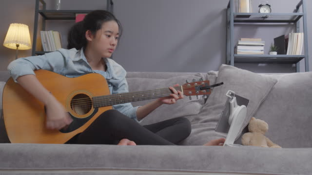 asian young girl playing acoustic guitar and learning with online lesson at home. teenager using laptop computer searching music note for practice her skill while staying at home with coronavirus or covid-19 lockdown situation - tutorial stock videos & royalty-free footage