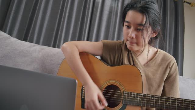 asiatische junge mädchen spielen akustische gitarre und lernen mit online-unterricht zu hause. teenager mit laptop-computer suchen musik-note für praxis ihre fähigkeiten, während zu hause mit coronavirus oder covid-19 sperrsituation - gitarrist stock-videos und b-roll-filmmaterial