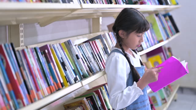asian young girl reading and looking at book in school library with shelf of books - bookshelf stock videos & royalty-free footage